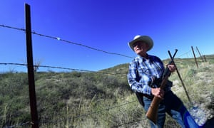 Cattle rancher Jim Chilton stands beside a barbed-wire fence that is all that separates Us and Mexico near Arivaca, Arizona