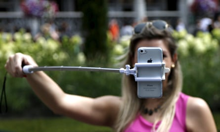 A woman holding a mobile phone on a selfie stick in front of her face