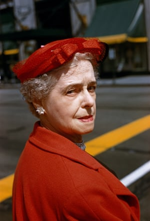 A woman in a red coat and hat looking back over her shoulder at the camera