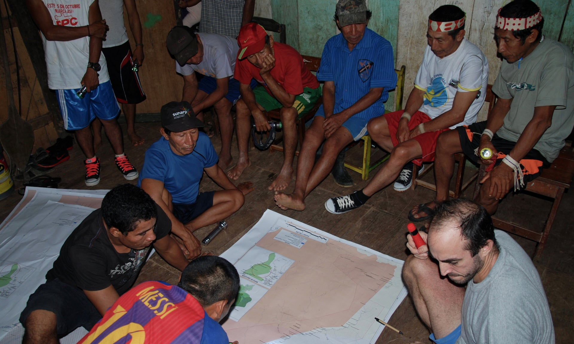 In Buenas Lomas Nueva village traditional healers, together with Segundo, Felipe and Acaté field coordinator David Fleck, review the draft maps of Matsés territory. Photograph: Acate Amazon Conservation