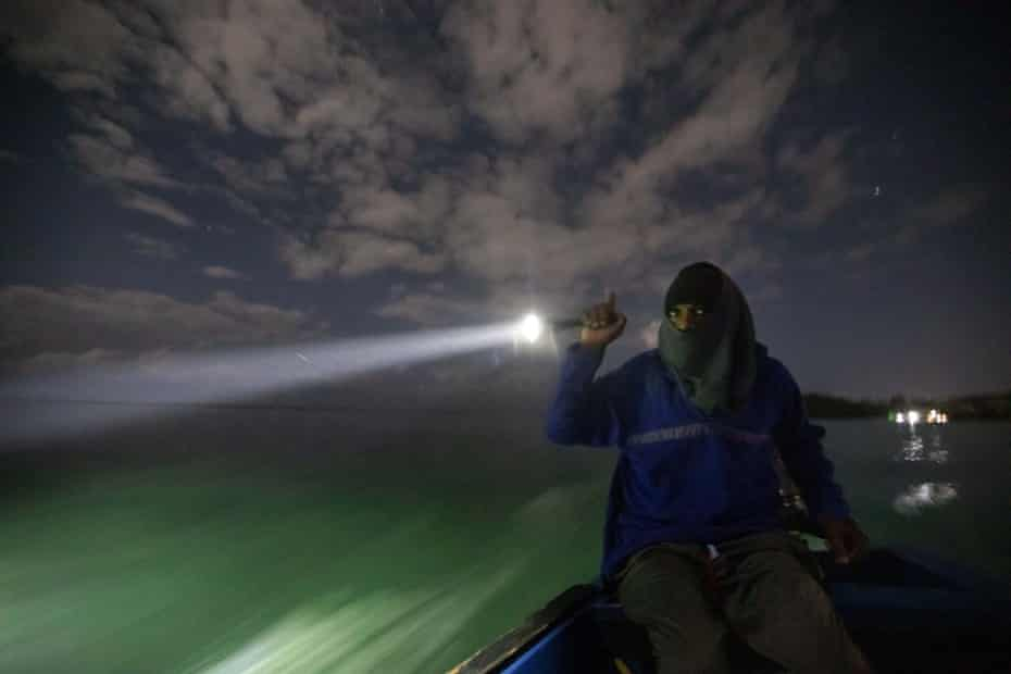 White River Fish Sanctuary warden Mark Lobban shines a spotlight on the protected reef while patrolling the no-take zone