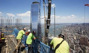Workers guide a boom pouring concrete on top of 3 World Trade Center in New York. Behind them is One World Trade Center.