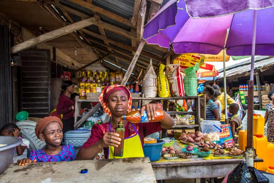 Comfort Oluwatuyi selling palm oil in a grocery shop in the camp market