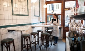 The narrow dining area with stools at small tables attached to the white tiled walls and a waitress in a white apron setting out glasses