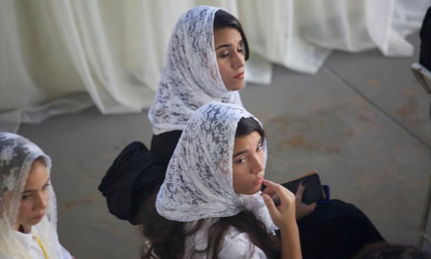 Women sat on one side of the aisle, their heads – even the youngest girls – covered in scarves. Photograph: Jonathan Watts for the Guardian