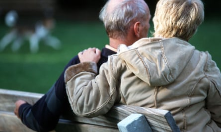 Worried pensioner couple sit on park bench.
