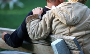 Back view of older couple sitting on park bench