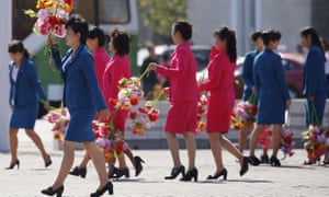 Women carry decorative flowers in preparation for Saturday's party. North Korea