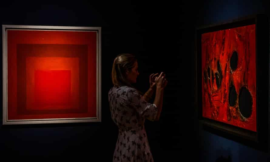 A visitor to Christie's in London between Homage to the Square: Between 2 Scarlets by Josef Albers and Rosso Plastica by Alberto Burri.