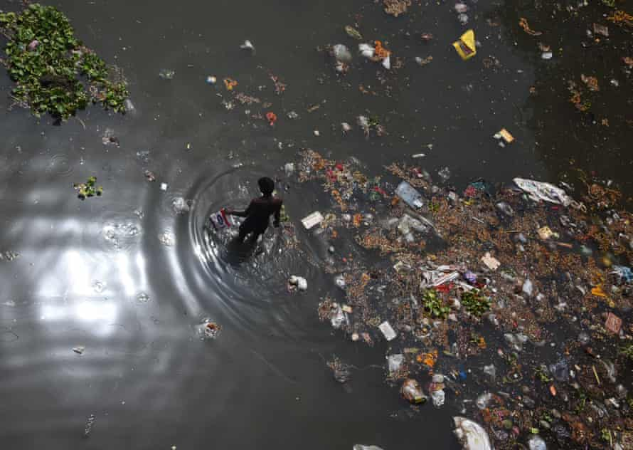 A man looks for recyclable items on the banks of the Yamuna, on the outskirts of New Delhi.