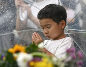 A boy prays in front of the cenotaph in the park
