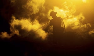 A firefighter sprays water on a leveled home as the Hillside fire burns in San Bernardino, on 31 October 2019. Whipped by strong wind, the blaze destroyed multiple residences.