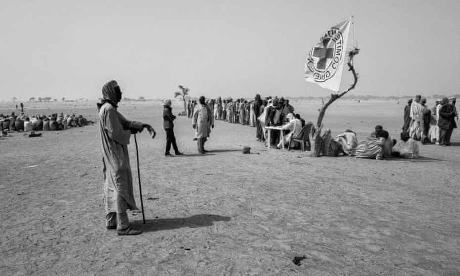People wait for food distribution by ICRC in Toumour camp where 47 thousand Nigerian refugees and internally displaced Nigerians took shelter in southeastern Niger.