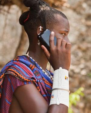 A Maasai man using a smartphone
