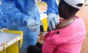 A Congolese health worker vaccinates a woman who had contact with an Ebola sufferer in the village of Mangina in North Kivu province of the Democratic Republic of Congo.