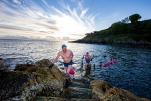 Open water swimmers take an early morning dip today at Brompton in Bangor, County Down, after restrictions in Northern Ireland eased, allowing the full return to outdoor sport.