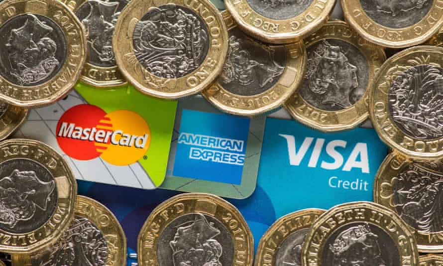 Mastercard, American Express and Visa credit cards with UK one pound coins