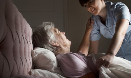 A personal care assistant attends to an elderly woman lying in bed.