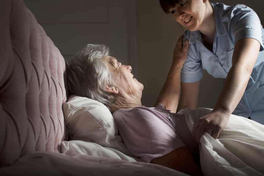 An elderly woman is tucked into bed at home by a care assistant