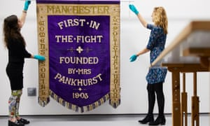 Conservators at the People's History Museum in Manchester unfurl a rare suffragette banner.