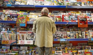 Rear view of a man standing and reading magazines in a branch of WH Smith