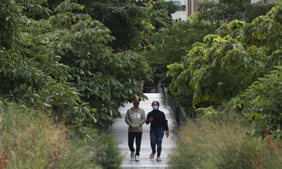 Two people walk down an overgrown path