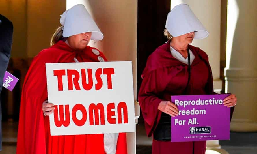 Women in Handmaid's Tale costumes with signs reading 'Trust women' and 'Reproductive freedom for all'.