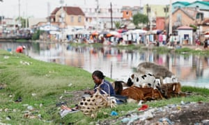 A woman sits with her sheep along the Andriantany waste water channel in Antananarivo.