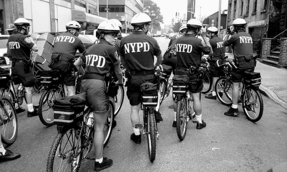 Midtown South Precinct's new bicycle patrol hits the streets. Police Officer Jeanie McCabe, the only female in the squad, looks over her shoulder.