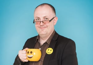 dean burnett smiling wearing a smiley badge and holding a smiley cup