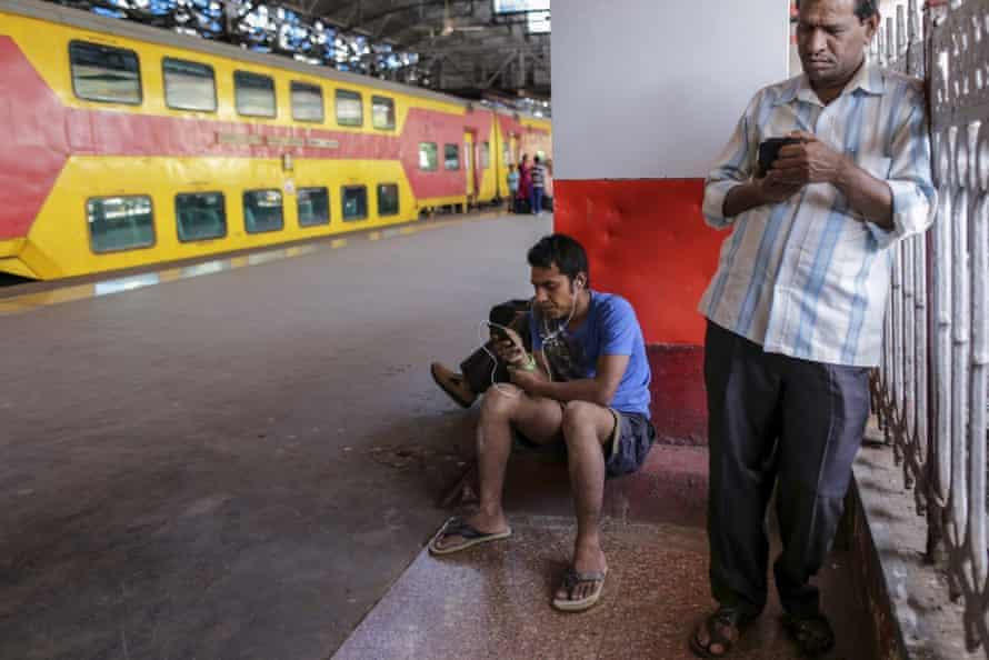 Passengers use smartphones at Mumbai Central railway station.