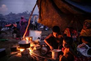 Rohingya children eat food at their makeshift tent at Tangkhali, Ukhiya