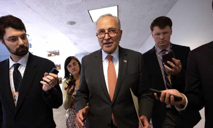 chuck schumer surrounded by reporters