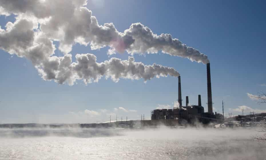 Coal-fired power plant in winter with emissions blowing