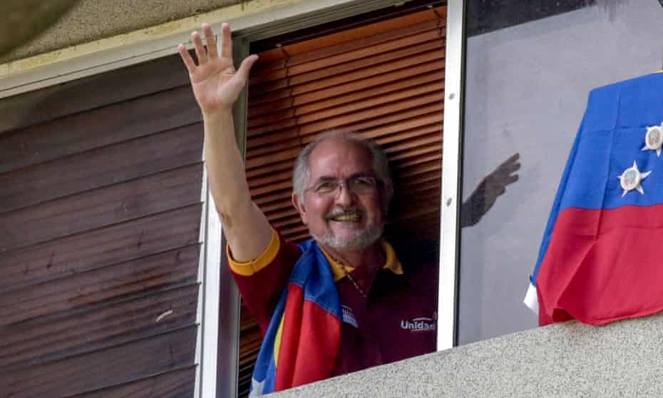 Antonio Ledezma waves from the window of his residence in Caracas, Venezuela, on 16 July 2017 where he was under house arrest. He has since fled to Colombia.