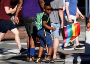 A boy carries a rainbow flag near the Stonewall Inn, on the eve of the LGBT Pride March, in the Greenwich Village section of New York City.