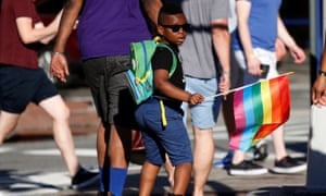 A boy carries a rainbow flag near The Stonewall Inn, on the eve of the LGBT Pride March, in New York City.