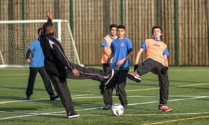 Students play football during a PE lesson at a school in Birmingham