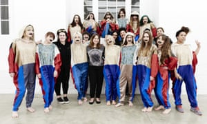 Deborah Coughlin and Gaggle. Twenty young women with faces painted white with black lips and wearing bright red and blue satin costumes, stand in a bright white room for a group portrait.