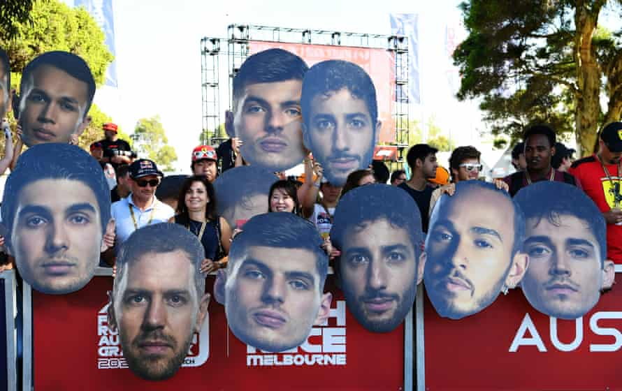 Fans hold up cutouts of their favourite drivers on the Melbourne Walk.