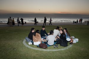 A group of students from Melbourne sit in a social distance circle to watch the sun go down on 2020