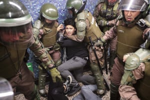 Police detain a protester at the Los Héroes metro station in the middle of a demonstration