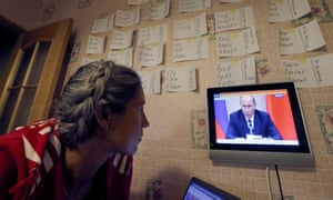 A woman watches President Vladimir Putin make a statement on airstrikes in Syria against the Islamic State.