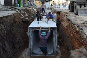 Hanoi, Vietnam. Workers install underground drainage on a city street