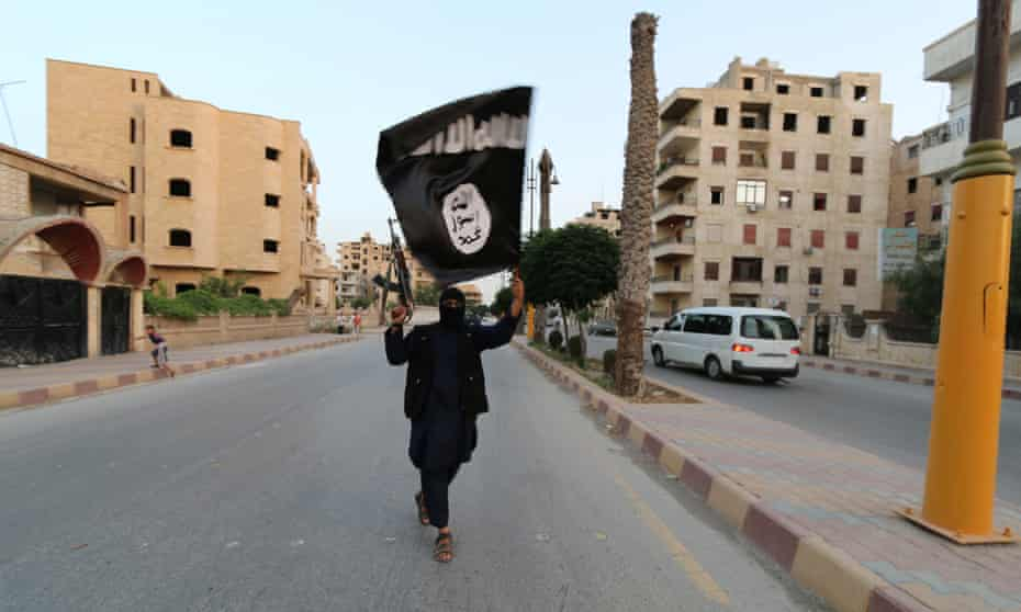 A fighter waves an Isis flag in Raqqa in June 2014
