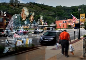 Images of coalminers are reflected in a window overlooking downtown Kittanning, Pennsylvania, in 2017.