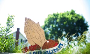 A wooden sign of praying hands for the military in Ackermanville.