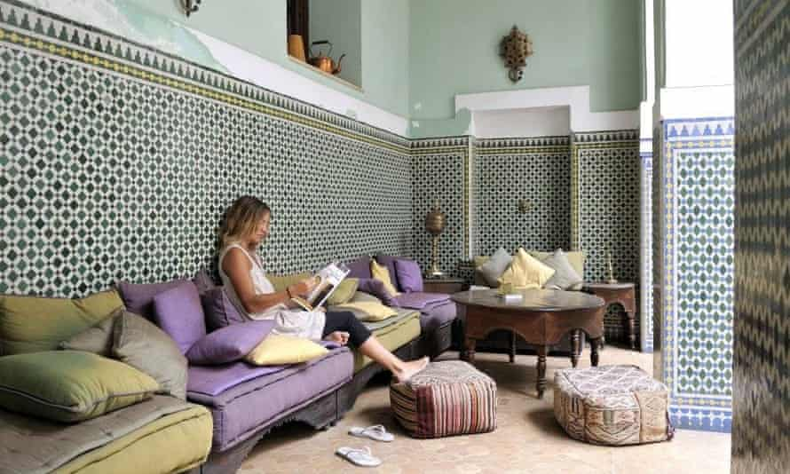 Woman relaxing and reading a book at the courtyard area of Equity Point Marrakech hostel, Morocco.