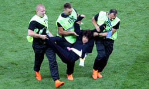 A woman is removed from the pitch during the World Cup final between France and Croatia.