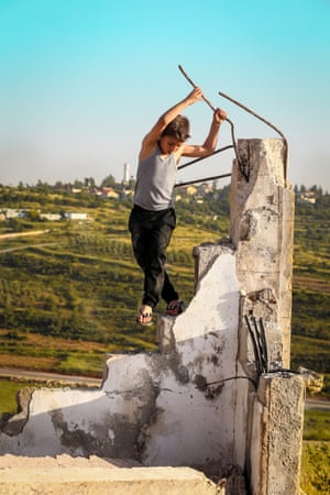 A child plays in the ruins of his house, in the West Bank